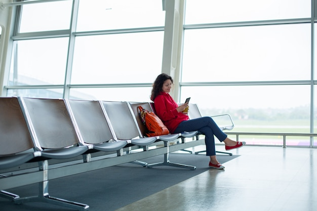 A girl is sitting on an empty row of seats in front of a large stained glass window in an airport terminal, waiting for a flight