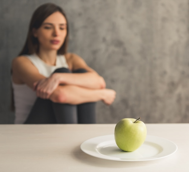 Girl is sitting in front of the plate with an apple.