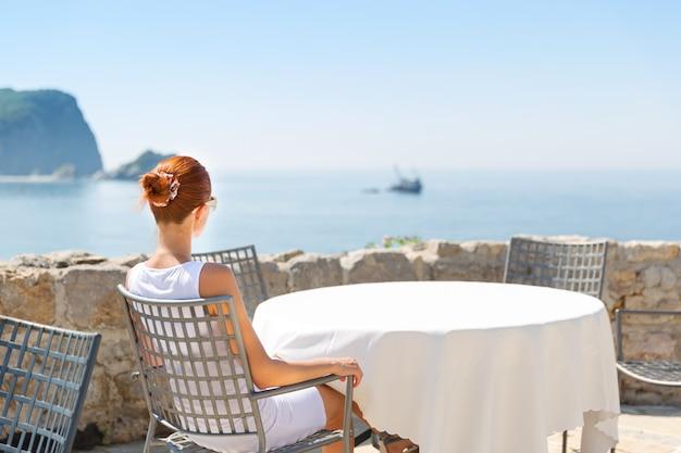 女の子は山の景色を望むモンテネグロの高級ホテルの海の見えるテラスの前に座っています