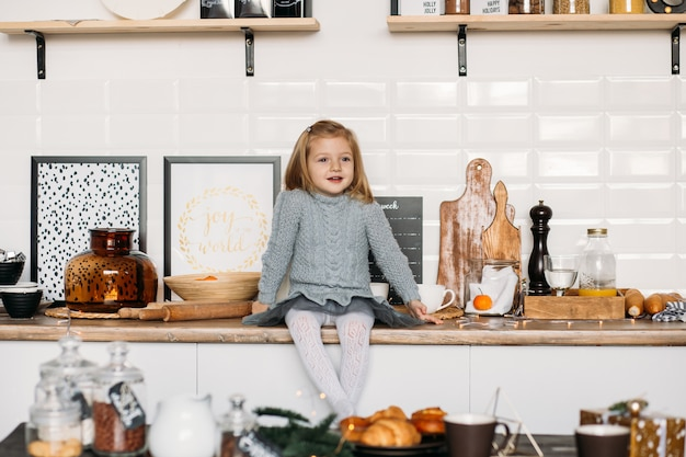 Girl is sitting on kitchen table