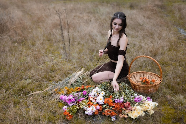 The girl is sitting next to a lot of flowers in the field
