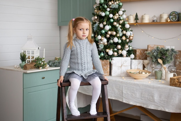 Girl is sitting near decorated christmas tree in kitchen indoors.