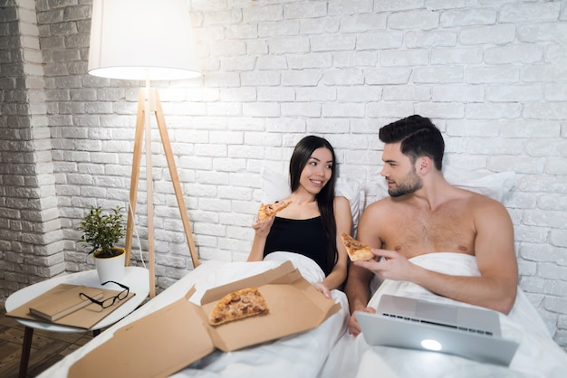Girl is sitting near man and they are eating pizza in bed.