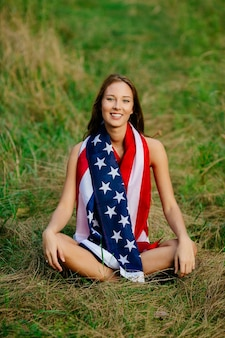 Girl is sitting on the grass with the American flag