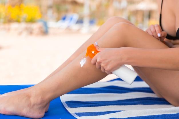 Девушка сидит на шезлонге и наносит крем для загара на ногу на пляже.
