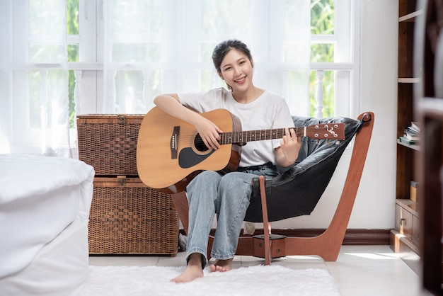 The girl is sitting and playing the guitar on the chair.
