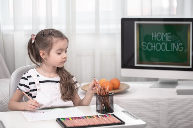 The girl is sitting at the table and doing homework. the child learns at home. home schooling and education concept.