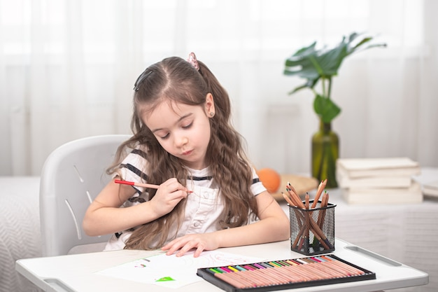 The girl is sitting at the table and doing homework. the child learns at home. home schooling