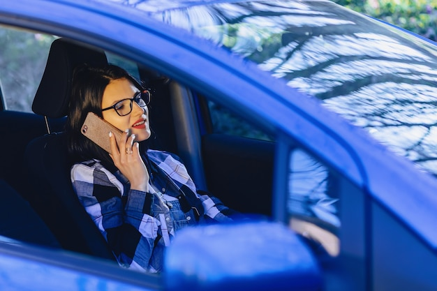 Girl is sitting at wheel of car and talking by phone