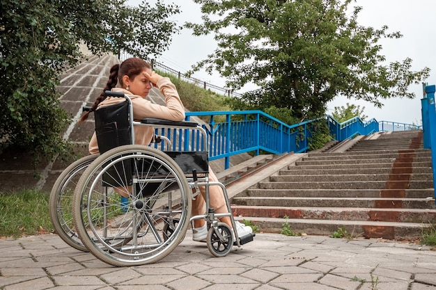 The girl is sitting in a wheelchair facing difficulties alone, depressed. the concept of a wheelchair, disabled person, full life, paralyzed, disabled person, health care.