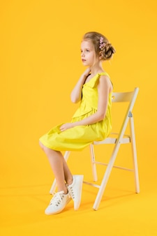 A girl is sitting on a white chair on a yellow background.