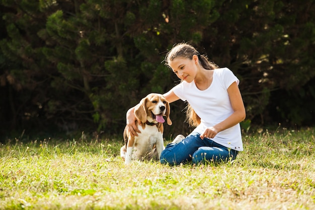Girl is sitting with beagle dog on the grass