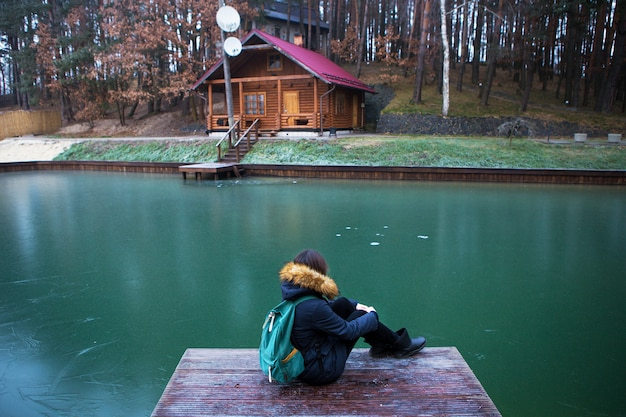 The girl is sitting with her back on a wooden bridge in a pine forest