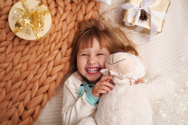 Девочка маленькая с дизайнерским одеялом из натуральной бежевой шерсти. смеющийся ребенок лежал на кровати.