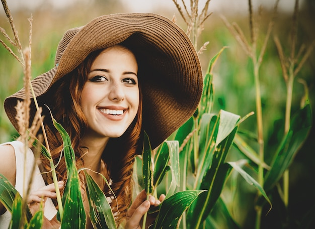 Girl is standing in a field of corn cobs