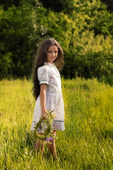 Girl is standing in the green grass, she made a wreath of flowers.