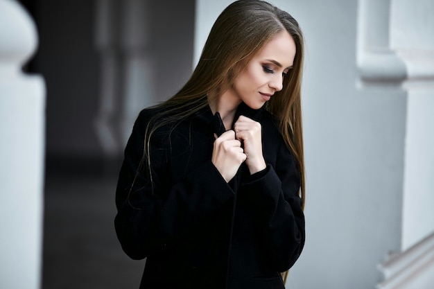 A girl is standing in profile and looking down.