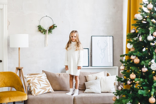 The girl is standing on the sofa, the room is decorated for christmas, the girl is wearing a light sweater and long hair
