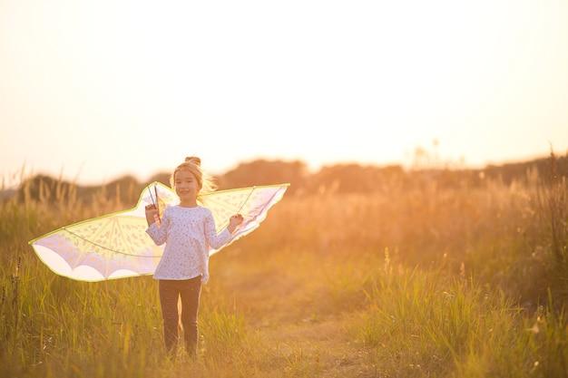 소녀는 들판에 날개를 달고 서서 연 날리기를 배우고 있습니다. 여름의 야외 엔터테인먼트, 자연과 신선한 공기. 어린 시절, 자유와 부주의. 아이들의 꿈과 희망