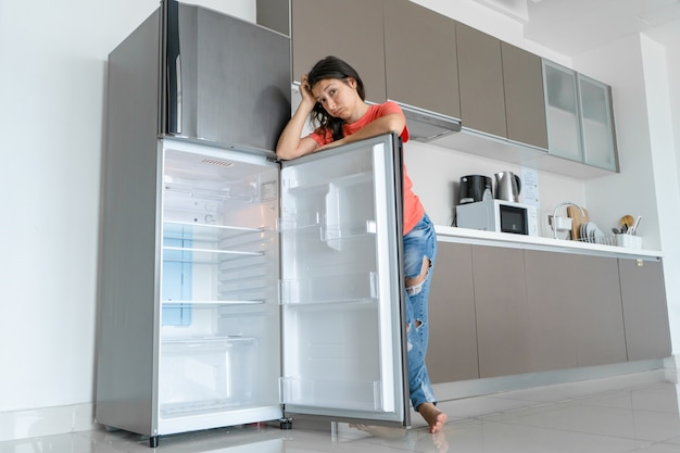 The girl is surprised at the empty refrigerator