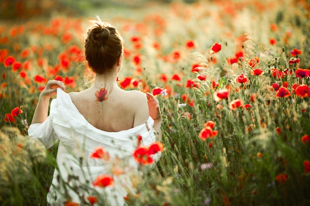 Girl is taking off the shirt from her back with a tattoo flower poppy on it, among the poppies field