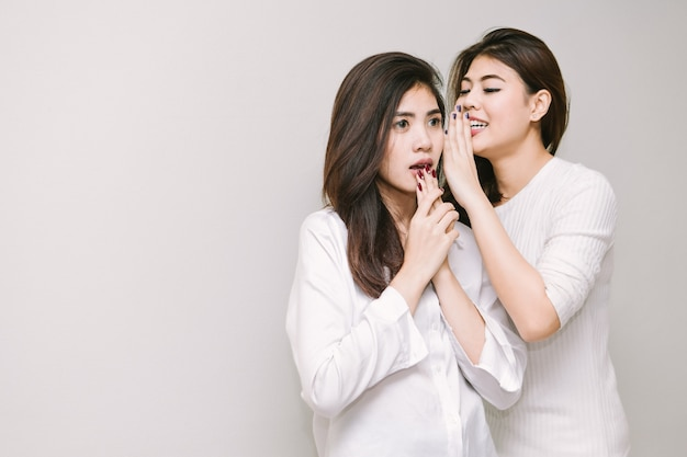 The girl is telling a secret to a friend