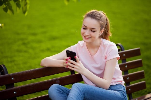 公園に座っている間、女の子は電話でテキストメッセージを送っています