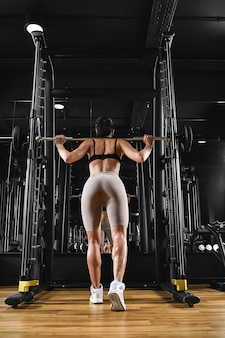 A girl is training her legs in the gym with a barbell sport lifestyle, keep fit, fitness motivation.