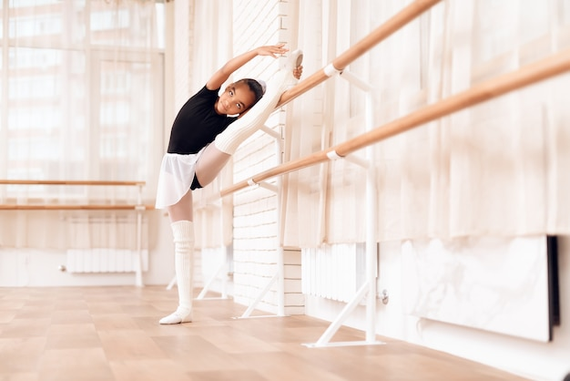 Girl is training a stretch of her legs near the ballet barr.