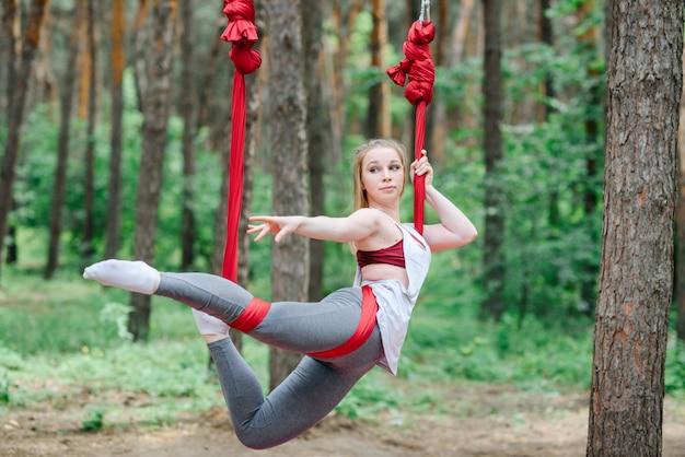 女の子はエアロヨガのハンモックでトレーニングしています。
