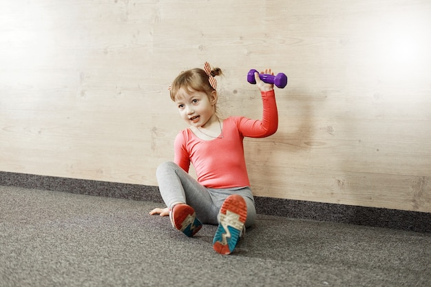 Girl is training with dumbbells in the gym