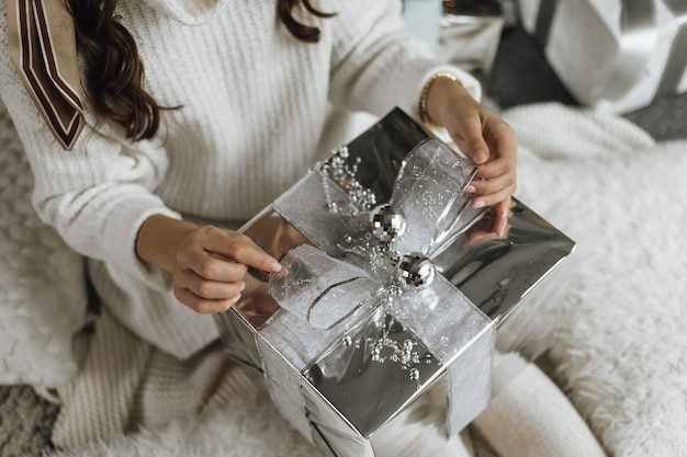 女の子は銀の紙とテープで贈り物を開梱しています