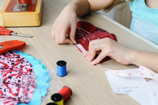 A girl is using a measuring tape to measure a dress for a doll