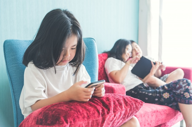 Girl is using a smartphone on chair mother enjoying with brother on sofa at home
