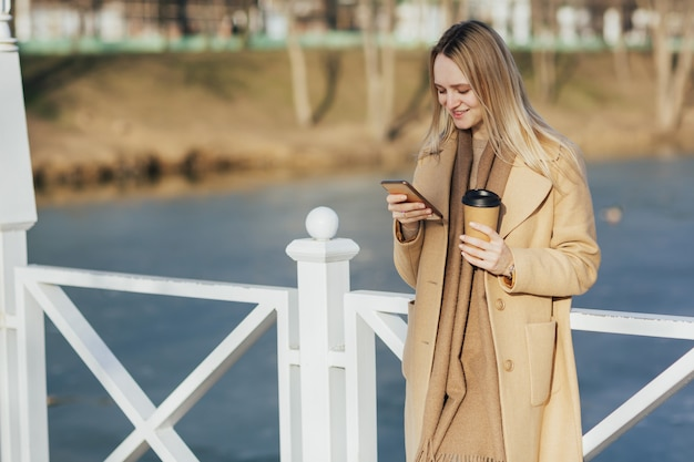 女の子は湖の近くの屋外でスマートフォンを使用しています