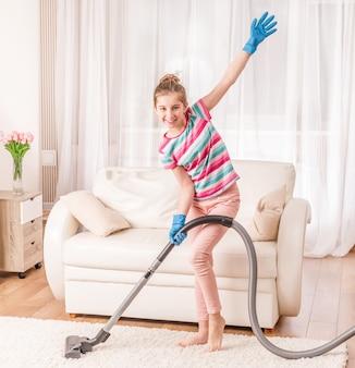 Girl is using vacuum cleaner