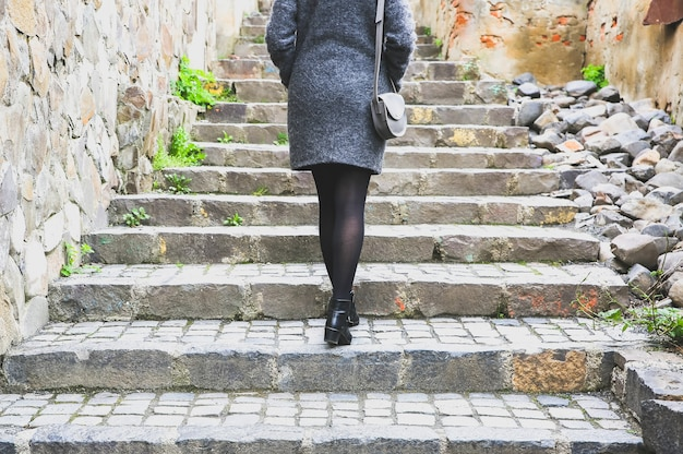 Девушка идет по узкой улице с каменной мостовой. стильная женщина с кожаной сумкой. лестница в городе.