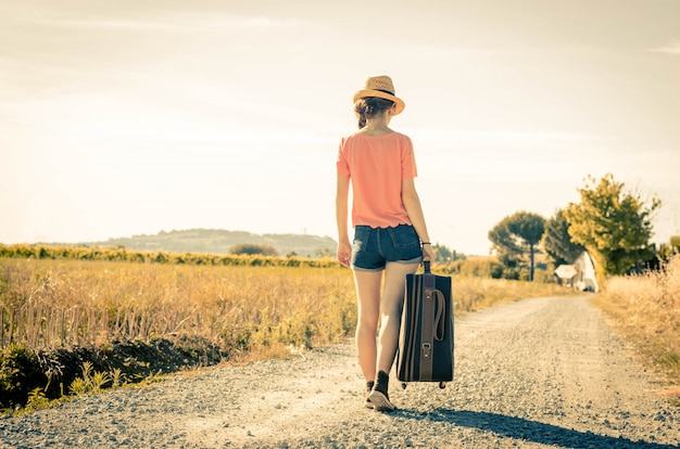 Girl is walking with her suitcase during her holiday - people, holidays and lifestyle concept
