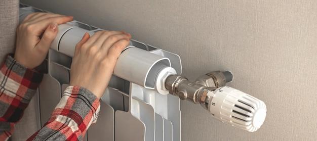 Девушка греется с помощью радиаторного обогревателя дома, фото дизайна баннера