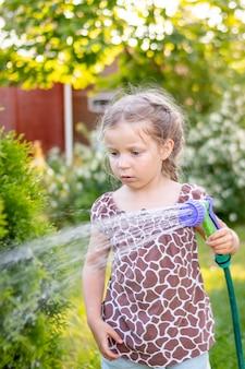 Девушка поливает цветы на лужайке возле коттеджа.