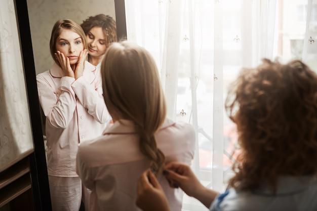 目を覚ました朝、顔が疲れてきて、女の子は見た目が気になります。鏡の近くに立っている2人の美しい白人女性。友人が髪型を作りながら待っているナイトウェアの金髪娘
