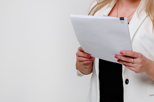 A girl in a jacket shrugs off a stack of papers and documents.
