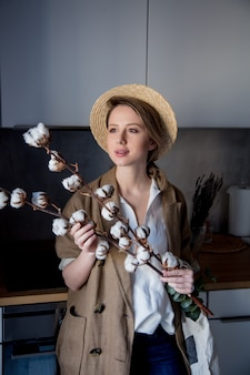 Girl in jacket with tote bag and cotton-plant in a kitchen