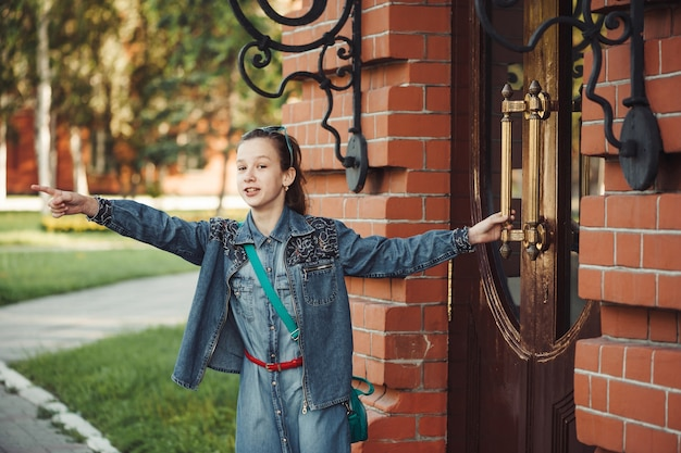 Girl in jeans clothes near old building of red brick