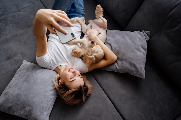 Girl in jeans is lying on her back on a gray sofa with a dog and is photographed on a smartphone