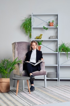 Girl in jeans and jacket sitting in livingroom with magazine