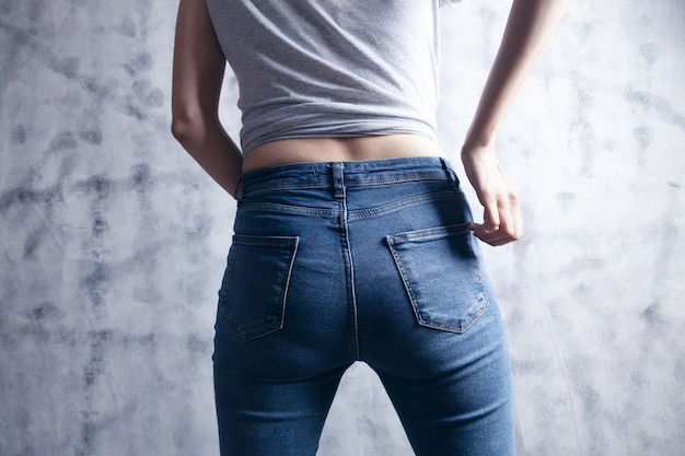 Girl in jeans posing. back view