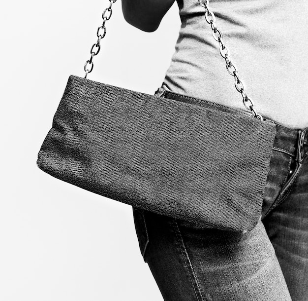 Girl in jeans with trendy clutch. black and white photo