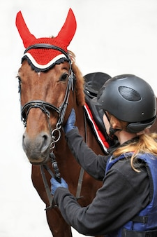Girl in a jockey outfit with a beautiful brown horse isolated on