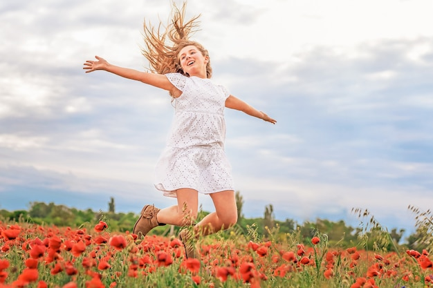 女の子は空とポピーのフィールドを高くジャンプします
